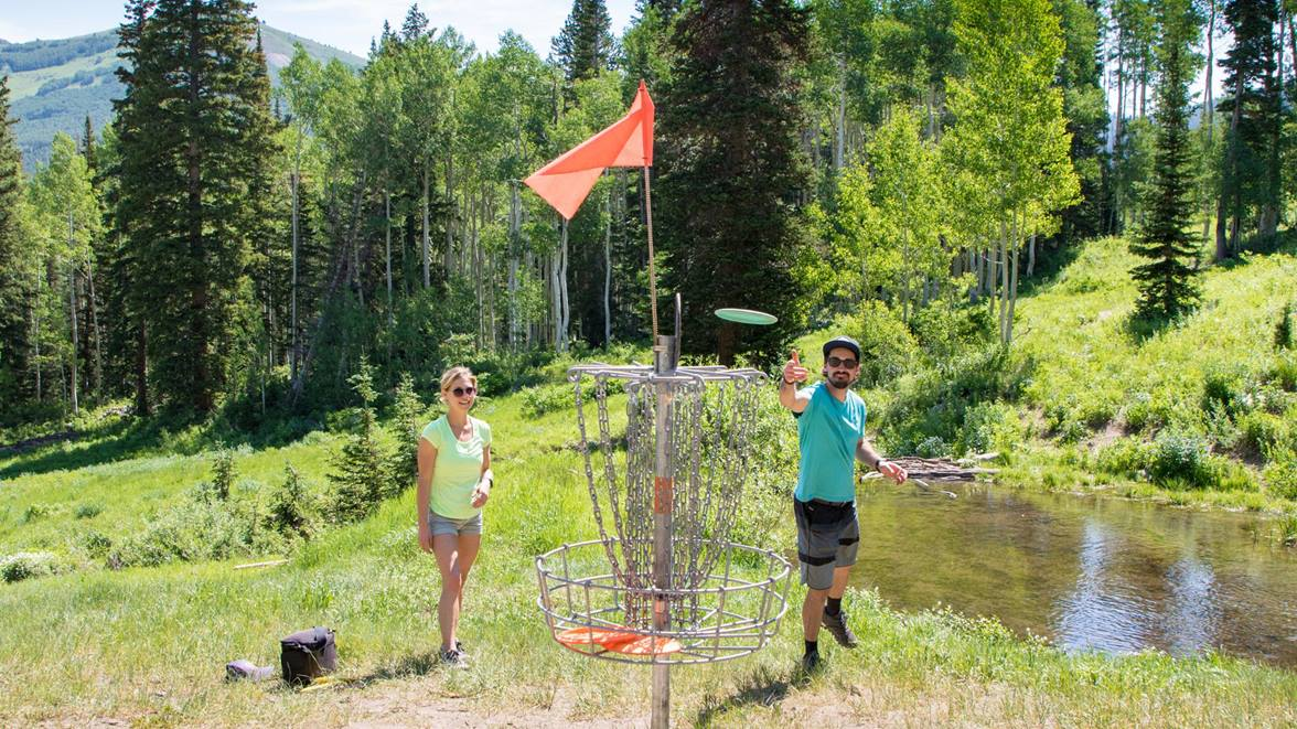 A couple playing disc golf throwing a disc at the basket